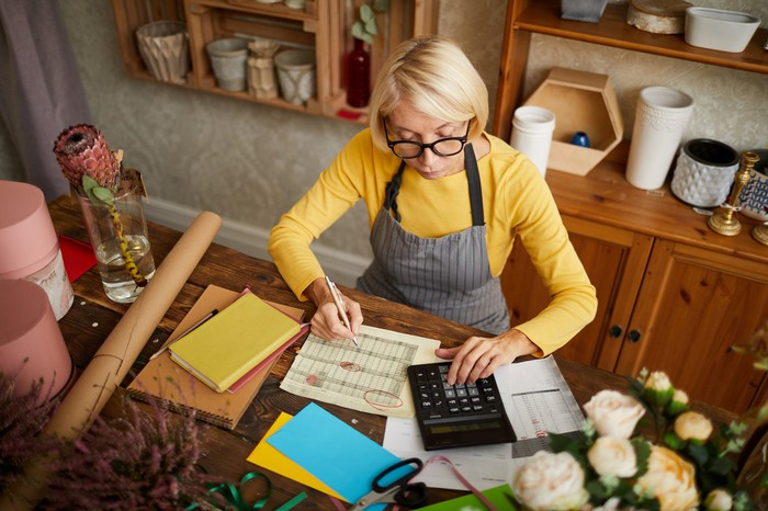 Woman in apron at table holding pen over document and typing on calculator