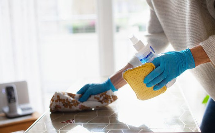 Person cleaning flat surface with sponge and rag