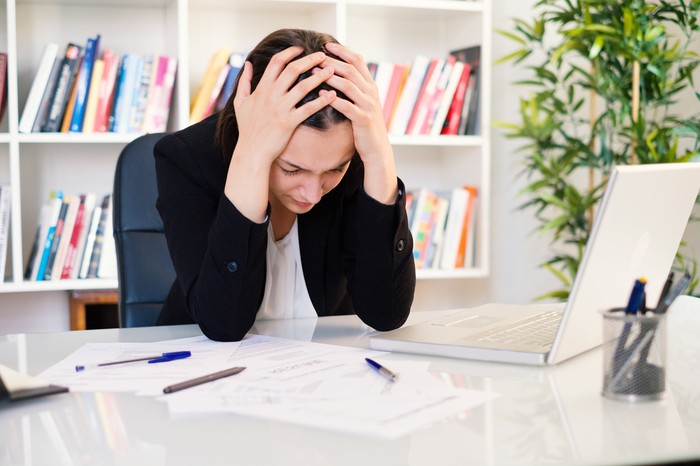 Woman holding her head in her hands at desk.