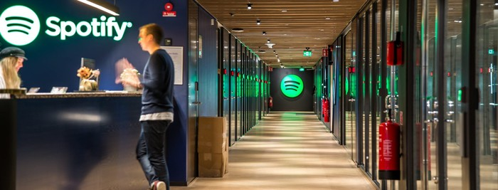 Interior of an office building. Reception desk has Spotify logo on the wall behind it.