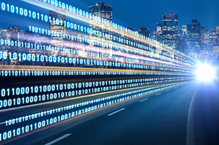 A photo of a city street at night with streams of digital data flowing above the concrete.