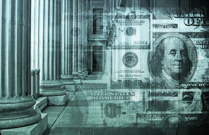 Hundred-dollar bills overlaid over architectural columns
