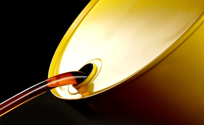 Oil pours from a golden oil drum.