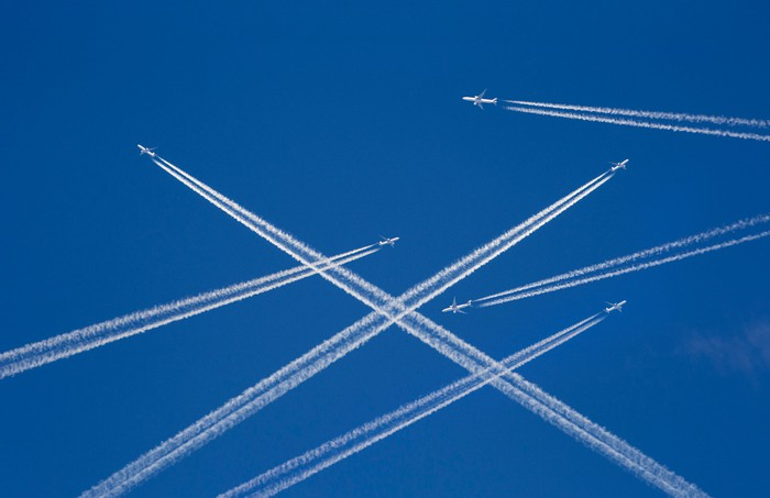 Airplanes and crisscrossing contrails in the sky.