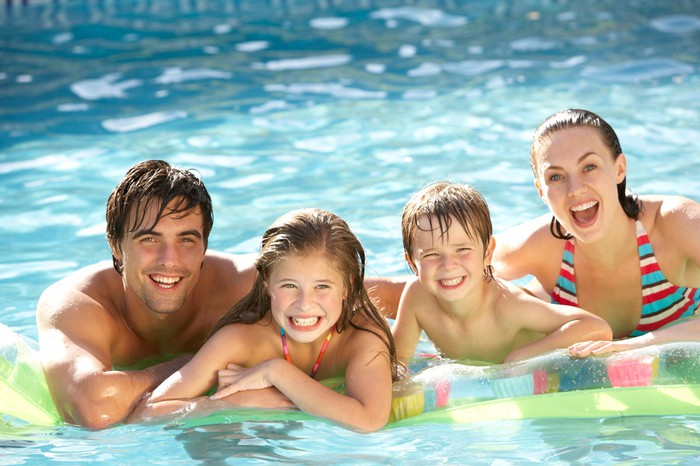 A family  in a swimming pool.