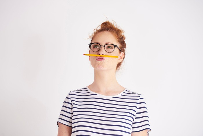 Woman holding pencil between her nose and upper lip.