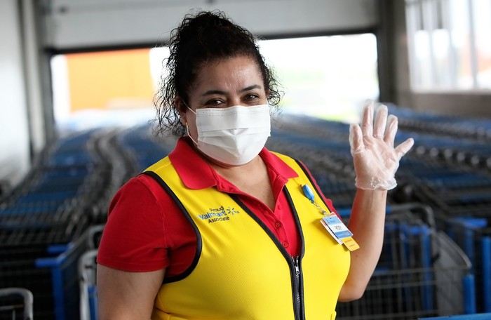 A Walmart associate wearing a yellow vest, face mask and rubber gloves.
