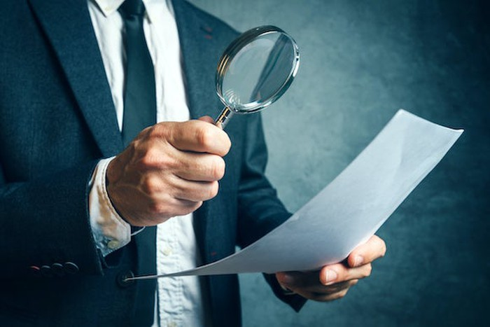 Man in business suit holding a magnifying glass to a piece of paper