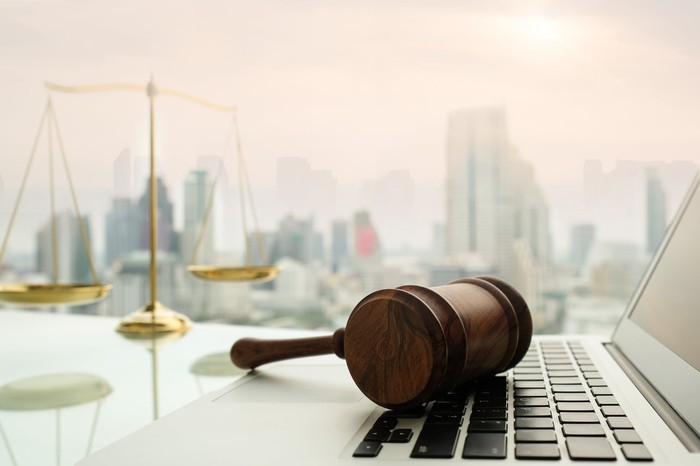 Gavel on laptop with scales of justice in the background against a cityscape.