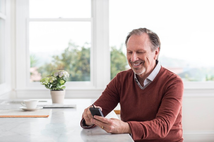 A man smiling while checking his blood sugar on a connected device.