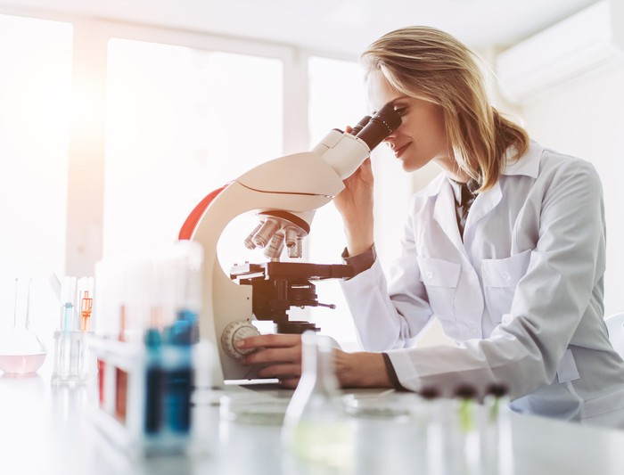 Blond woman in white lab coat using a microscope.