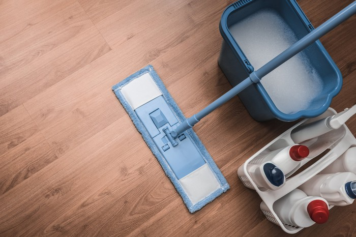 Mop with pail of water and cleaning solutions