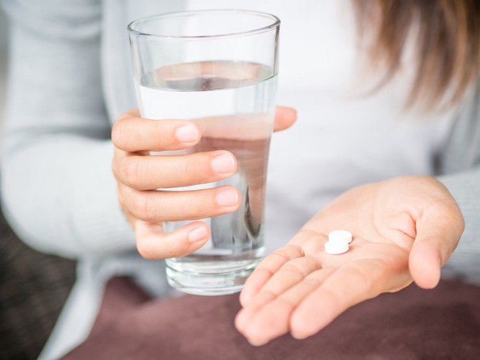 A woman holds a glass of water and shows two pills in her other hand.