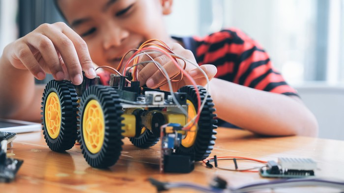 A little boy rewires a toy car.