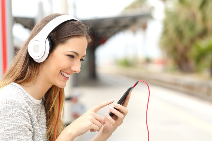 A woman wearing headphones looking at a smartphone.