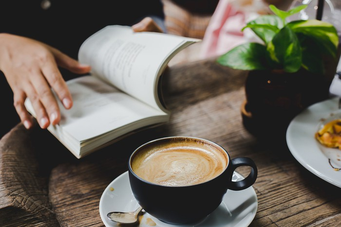 Person reading book with a cup of coffee beside them on table