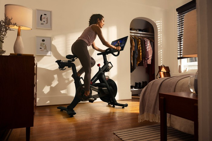 A woman rides a Peloton stationary bicycle in a bedroom.