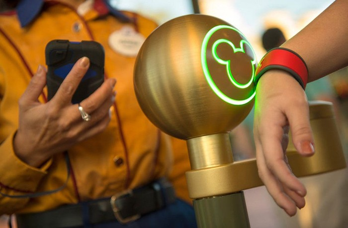 A guest wearing a MagicBand scans into a Disney World theme park turnstile.