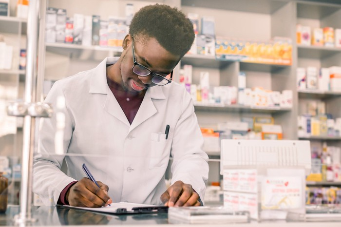 A pharmacist filling out a form behind the counter