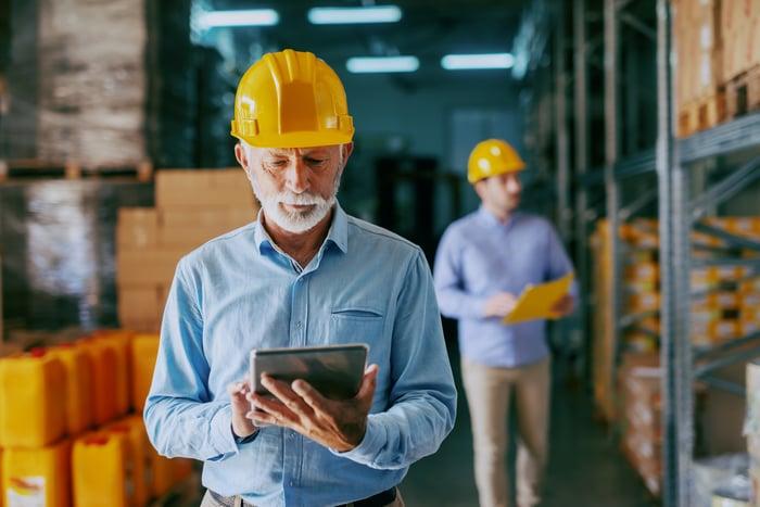 Older man wearing yellow helmet in warehouse looking at tablet