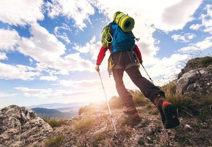 A backpacker with lots of gear hikes a mountain.