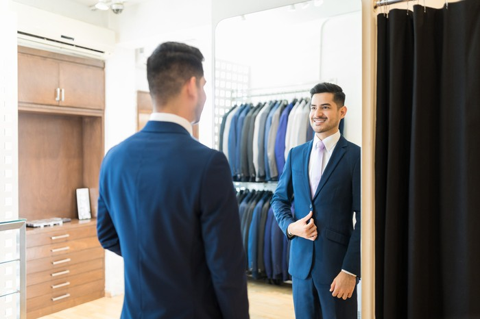 Man trying on a suit at a store.