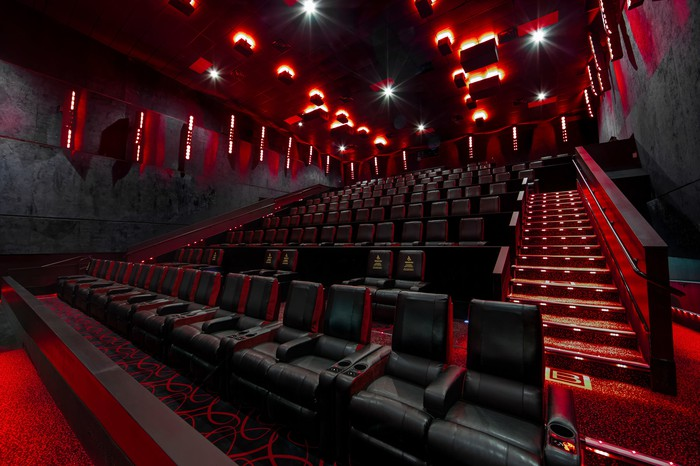 An empty, dimly lit theater with large reclining seats