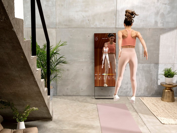 A woman exercising with a Mirror device.