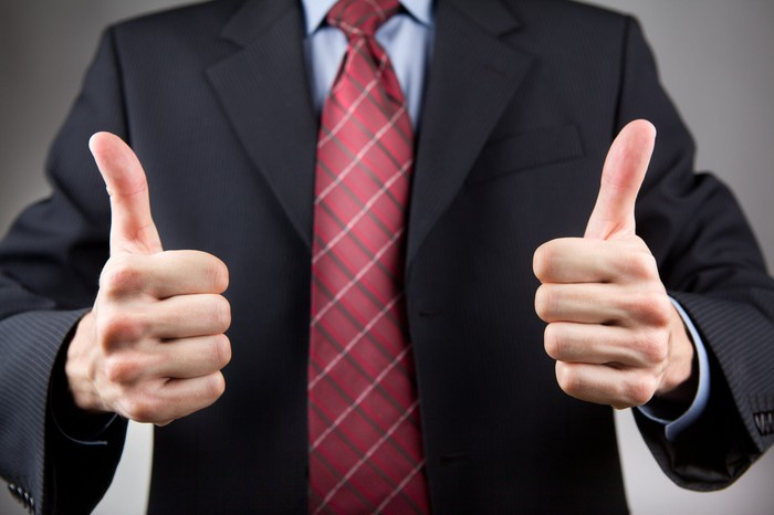 Man in suit showing two thumbs up.
