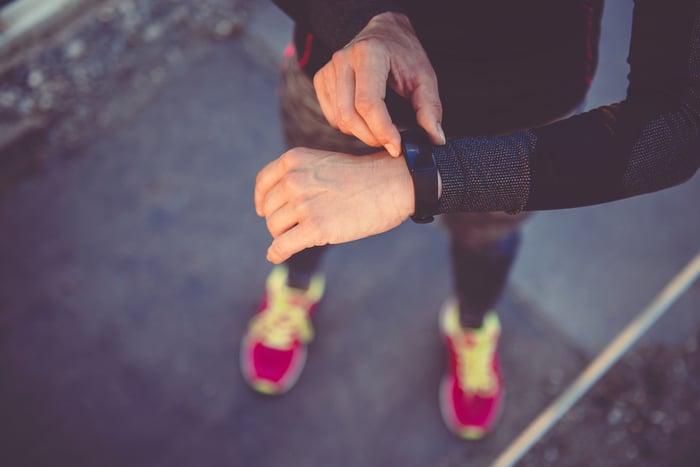 A woman checks her wristband fitness tracker.