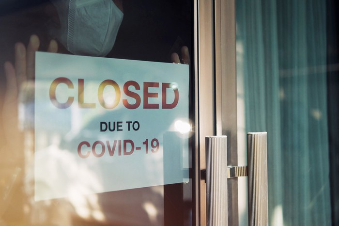 "A sign in a store window that says ""Closed Due to COVID-19."""