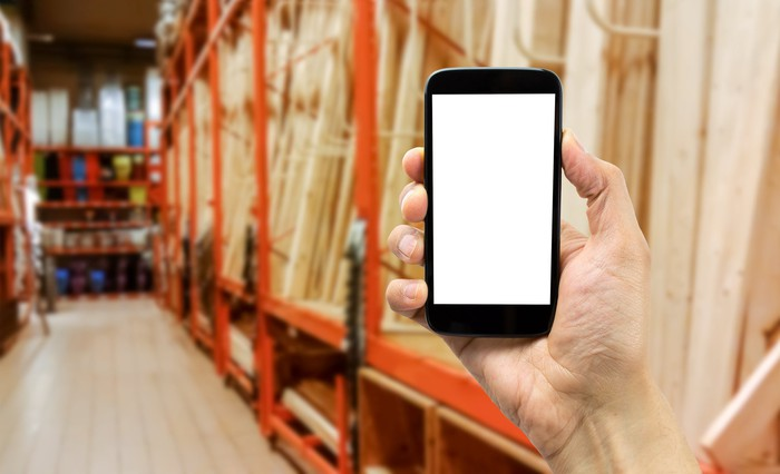A hand holding up a smartphone in the lumber section of a home-improvement store