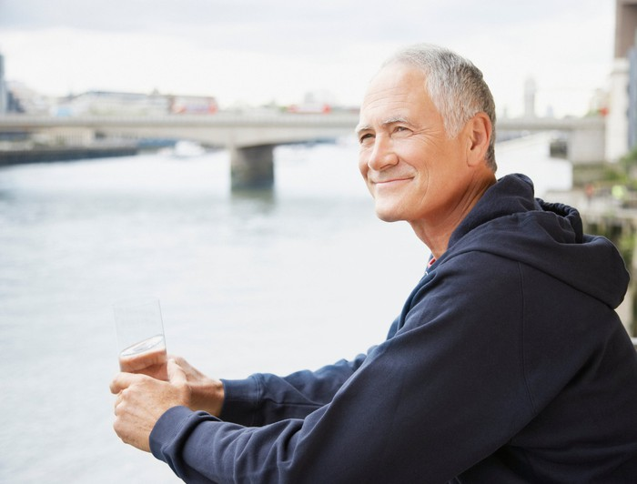 Older man by the water holding glass