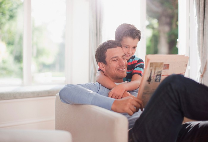 Man in armchair reading newspaper being hugged by young boy
