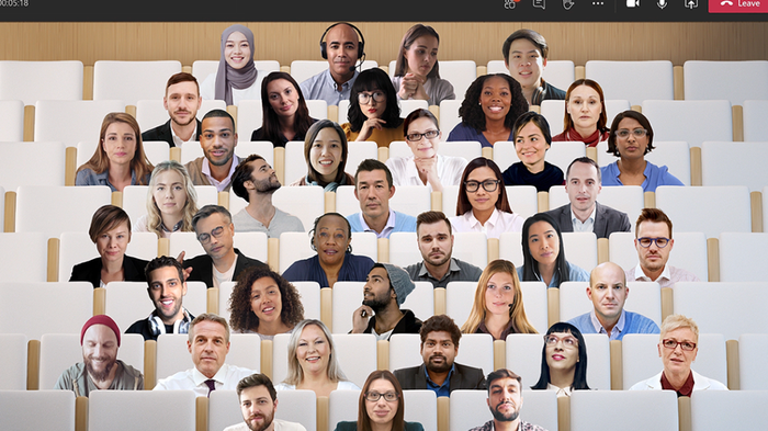 Images of a large number of people superimposed over an auditorium seating view in Team.