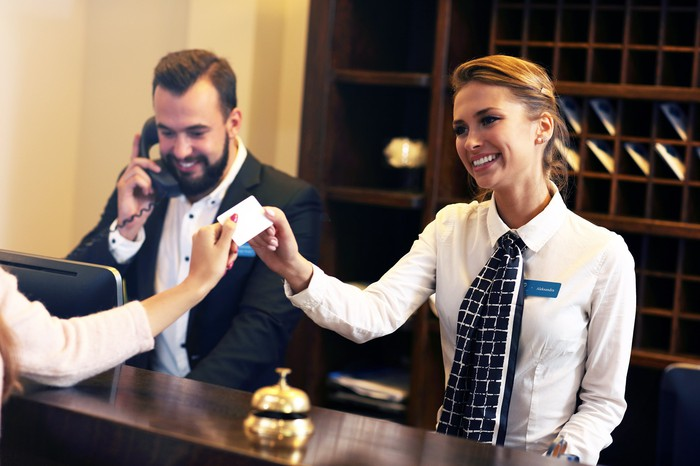 A female concierge smiles and takes a credit card from a guest at a hotel front desk.