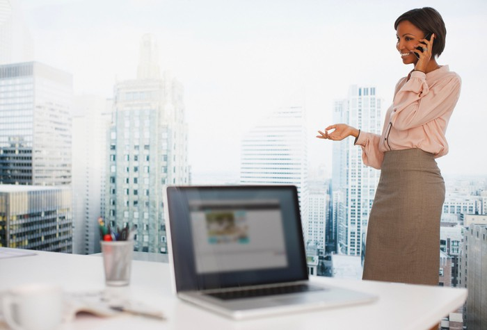 A smiling businesswoman talks on her phone in a home office with big-city views.