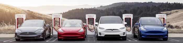 Several Tesla vehicles at a charging station.