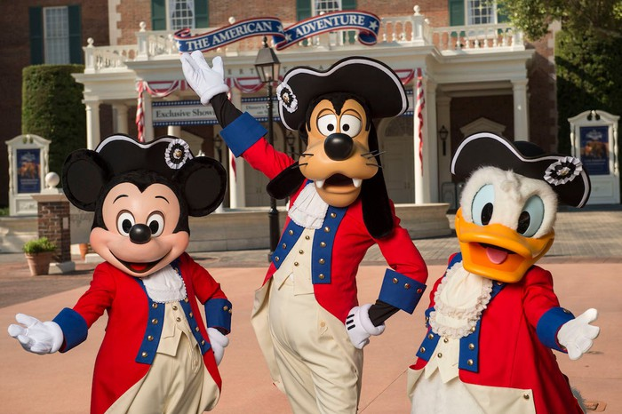 Mickey Mouse, Goofy, and Donald Duck in 1776 attire in front of Epcot's American Adventure attraction.