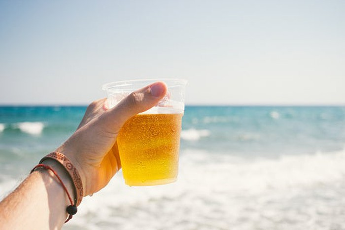 A hand holding a cup of beer on a beach