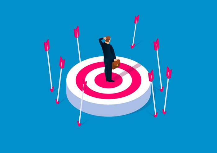 Businessman standing in the center of a target surrounded by arrows that missed their mark.