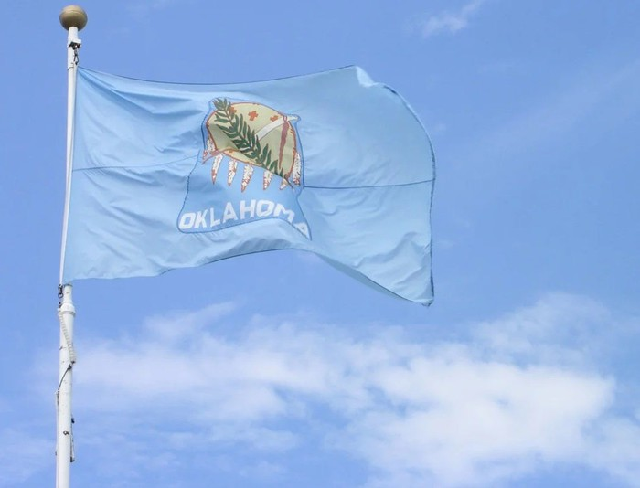 Oklahoma state flag flying on a flagpole against a blue sky with a few clouds.