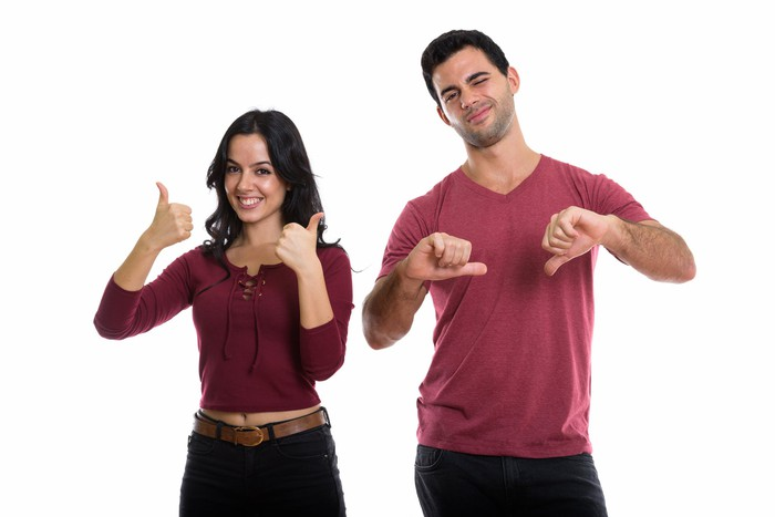 Woman giving two thumbs-up next to man giving two thumbs-down