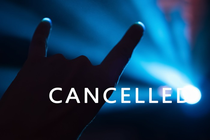 A hand doing the sign of the horns in the light of a spotlight, behind the word Cancelled.