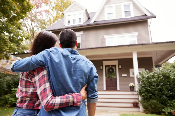 A home buyer couple hug in the front yard of their new house.
