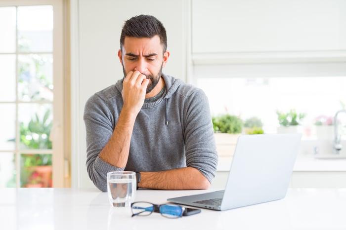 Man at laptop biting nails