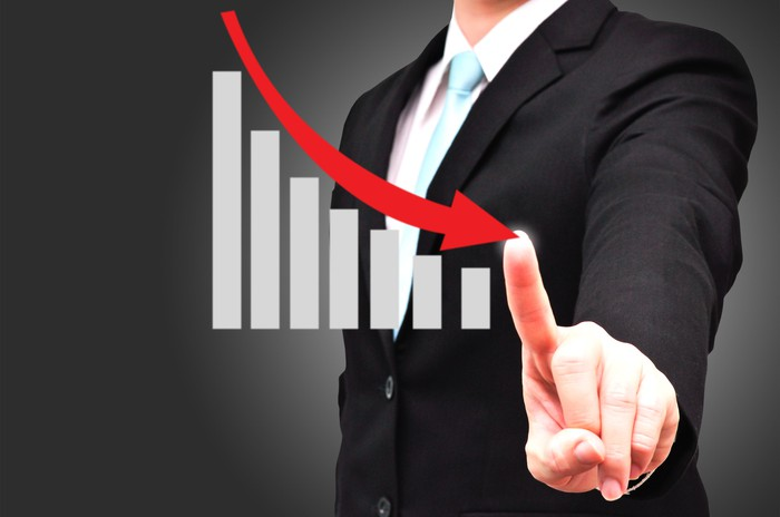 A man traces a downward arrow over a bar chart with his finger.