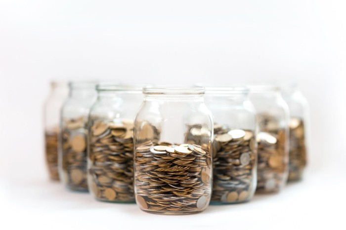 Seven glass jars filled with coins.