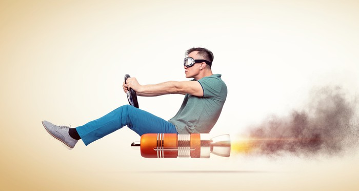 A man rides a rocket while holding a steering wheel.