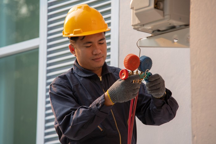 A commercial HVAC worker tests an air-conditioning and ventilation system.